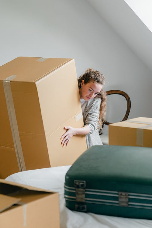 Female in casual clothes and ring on finger peeping out of big cardboard box while standing leaned forward near bed with suitcase in attic style room
