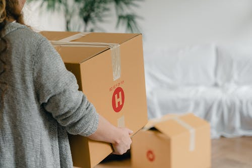 Crop anonymous woman holding big box near sofa in apartment