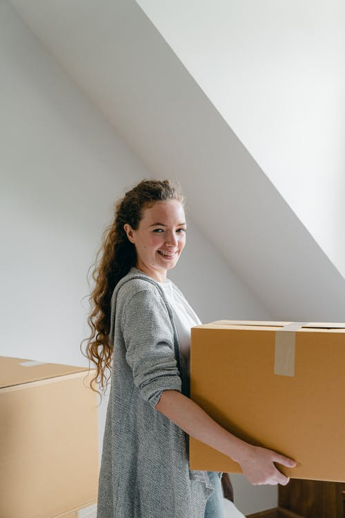 Smiling woman standing with big box in apartment