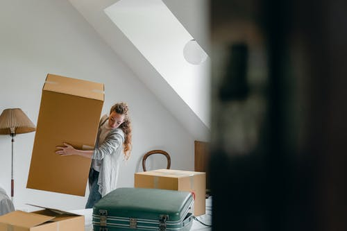 Woman carrying boxes in new apartment