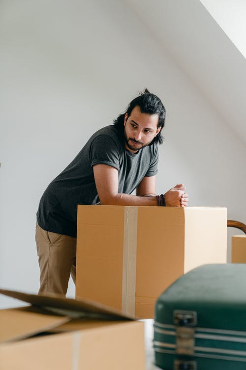 Pensive bearded male in casual clothes leaning on large carton box while moving to new house and looking away