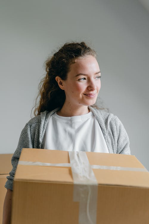 Smiling woman with carton box looking away