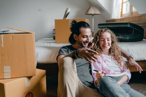 Cheerful couple taking notes while moving to new house