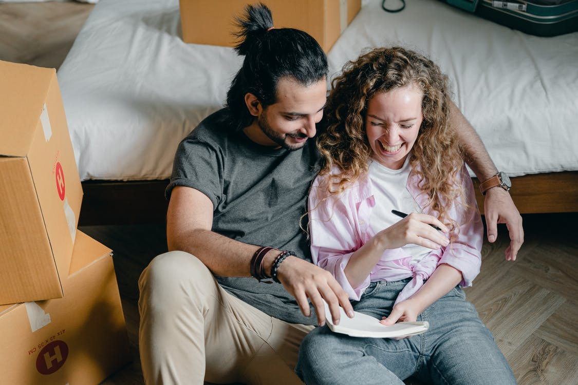 Cheerful couple with notebook moving house