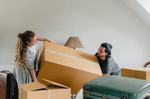 Man and woman carrying carton box