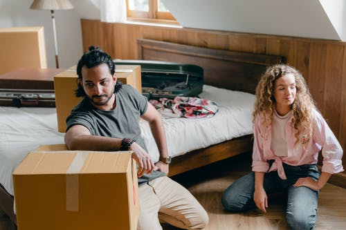 Calm adult ethnic man and woman in casual clothes sitting on floor near bed in attic bedroom while unpacking boxes and suitcases after relocation in new cozy apartment