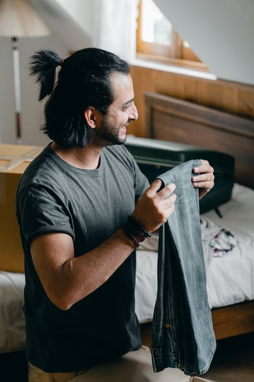 Smiling bearded ethnic male in casual t shirt taking out jeans from opened carton box while unpacking clothes in attic bedroom of new apartment after moving and looking away