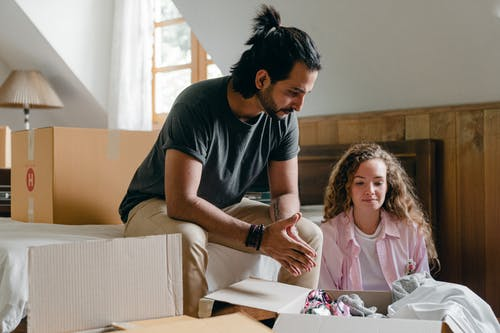 Diverse couple unpacking carton boxes during relocation at new home