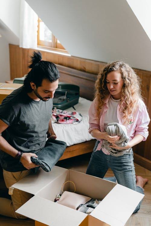 Diverse man and woman unpacking stuff while relocating to new apartment