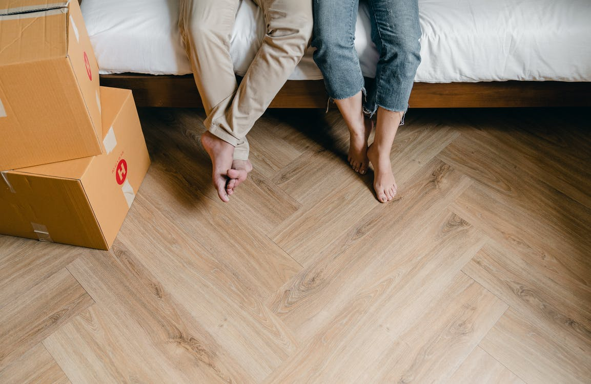Unrecognizable barefoot man and woman sitting on bed near carton boxes while relaxing from unboxing belongings during relocation in new flat