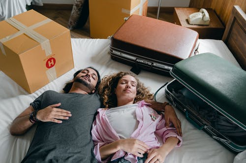 Sleeping diverse couple lying on bed during relocation in new house