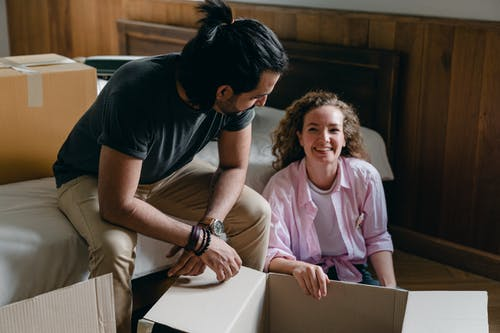 Diverse couple unpacking cardboard boxes while moving in new home