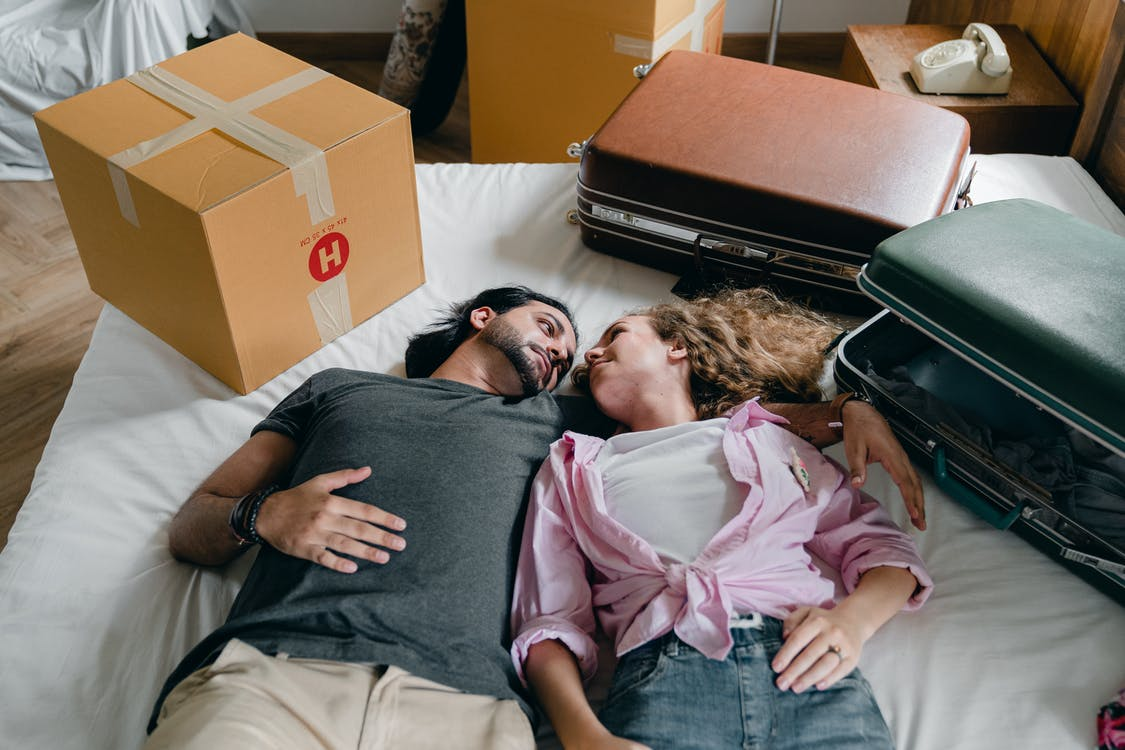 Embracing diverse couple lying on bed during relocation in new house