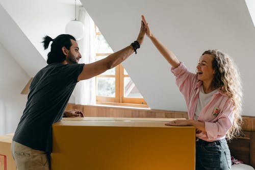 Exited diverse couple relocating in new apartment