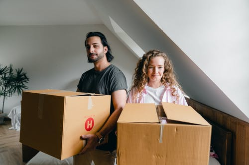 Young woman and ethnic man in casual clothes smiling at camera and holding big boxes during relocation to new apartment