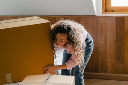 Young woman unpacking boxes in light apartment
