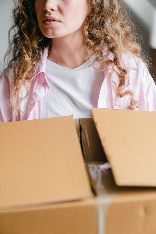 Crop serious young lady carrying carton box at home
