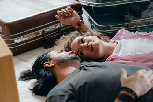 Multiethnic couple resting on bed in bedroom