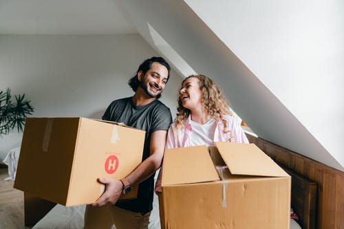 Content young woman and ethnic bearded man carrying cardboard boxes and laughing each other while unpacking belongings in new modern house