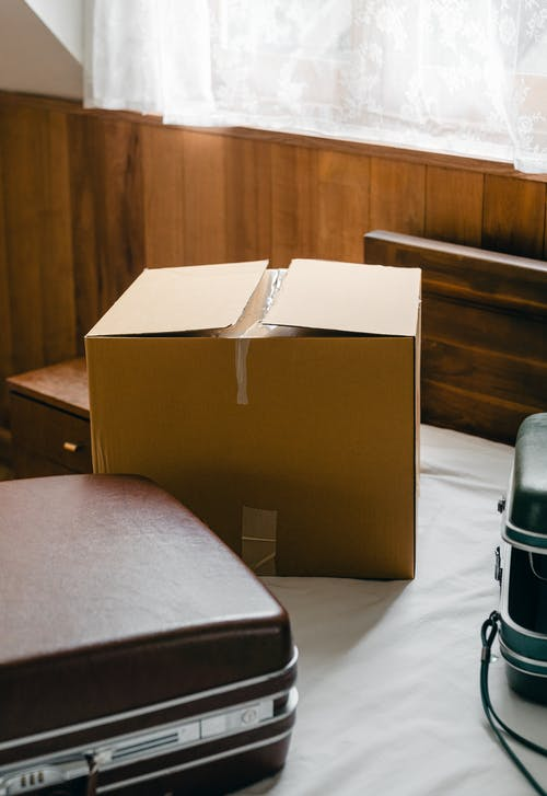 From above of modern suitcases placed near big cardboard box on bed in contemporary apartment