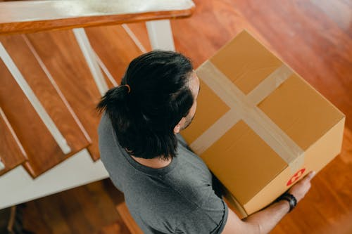 Man carrying box in new apartment