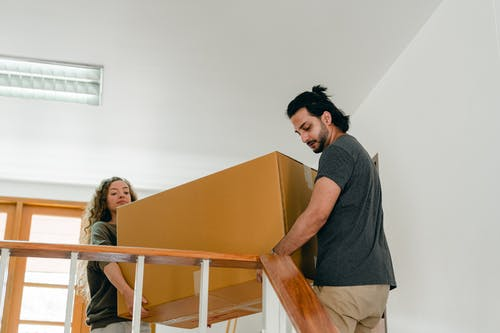 From below of couple in casual clothes carrying big carton box together while moving packed personal items into new apartment
