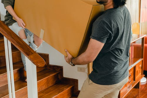 Couple carrying personal items box down stairs
