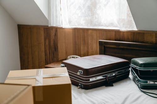 From above of brown and green vintage suitcases and packed carton boxes placed on bed with sheet in light room with sloping roof