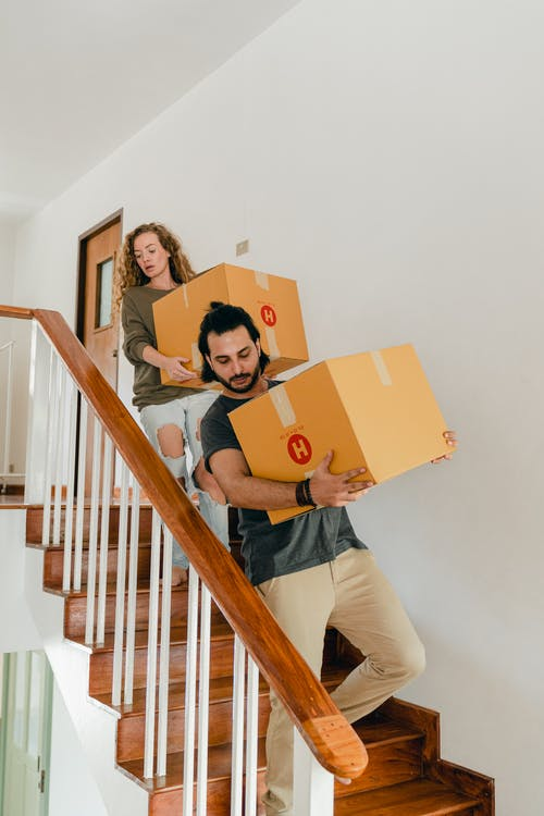 Focused couple carrying boxes on stairs