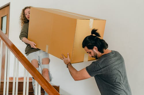 Couple carrying box down stairs in new apartment