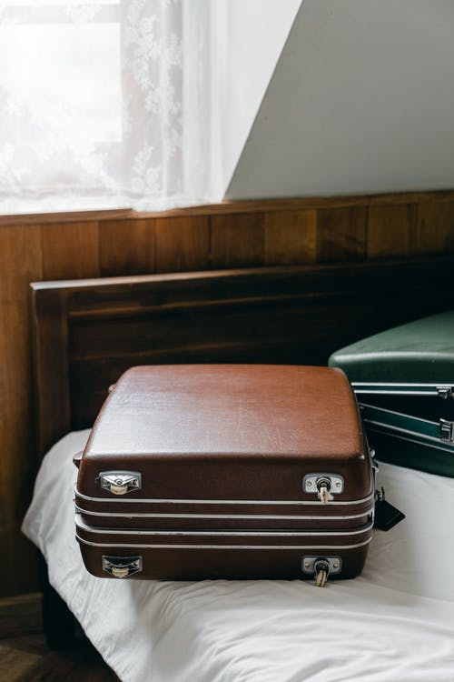 Suitcases placed on edge of bed
