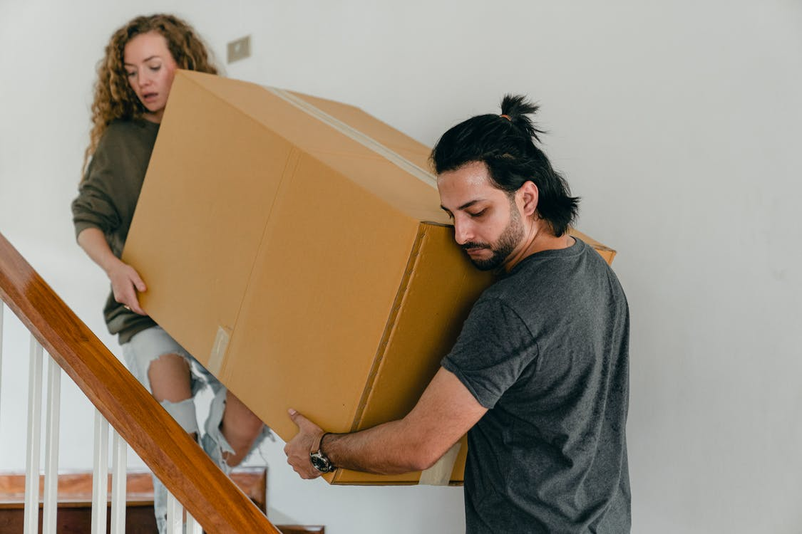 Concentrated couple carrying big carton box down stairs