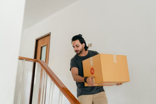 Adult man carrying box down stairs