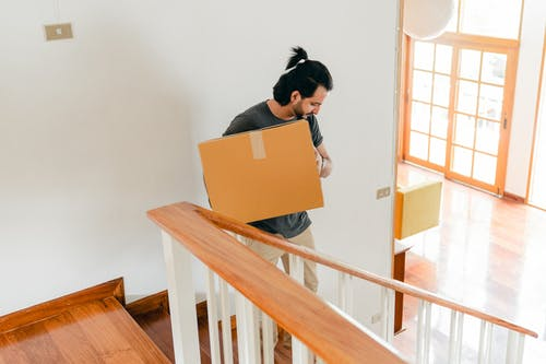 Adult man moving carton box to new house
