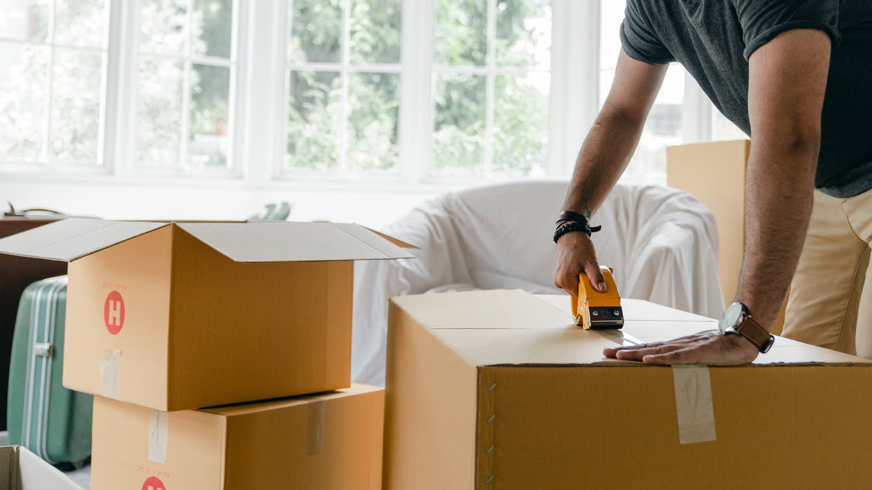 Crop unrecognizable man in casual clothes packing carton box using scotch tape dispenser for moving personal items to new apartment
