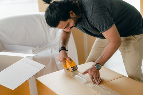 Adult man packing cardboard box with scotch tape dispenser