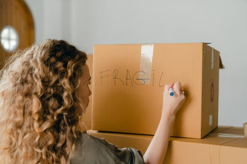 Back view of unrecognizable curvy female in casual clothes writing fragile on empty side of carton box while waiting for courier