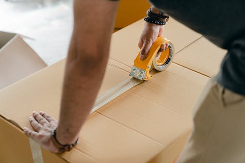 Crop faceless man packing box with scotch tape