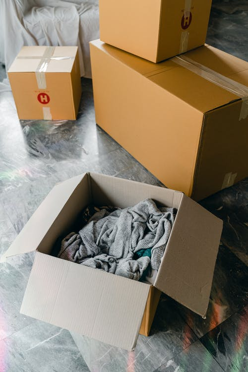 From above of cardboard boxes with packed items placed on floor in new apartment