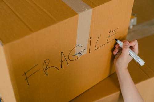 Crop person packing box with fragile items