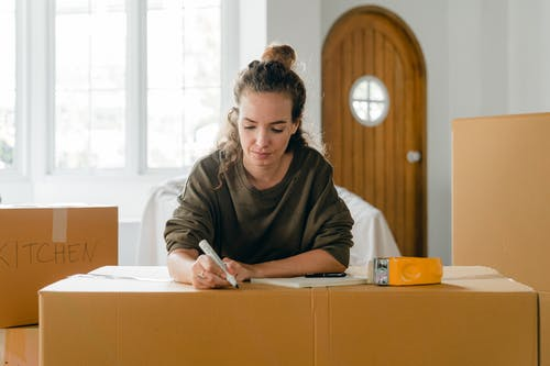 Concentrated young lady preparing carton boxes for relocation