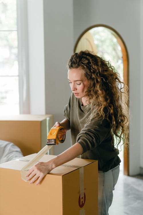 Concentrated young lady sealing cardboard boxes at home