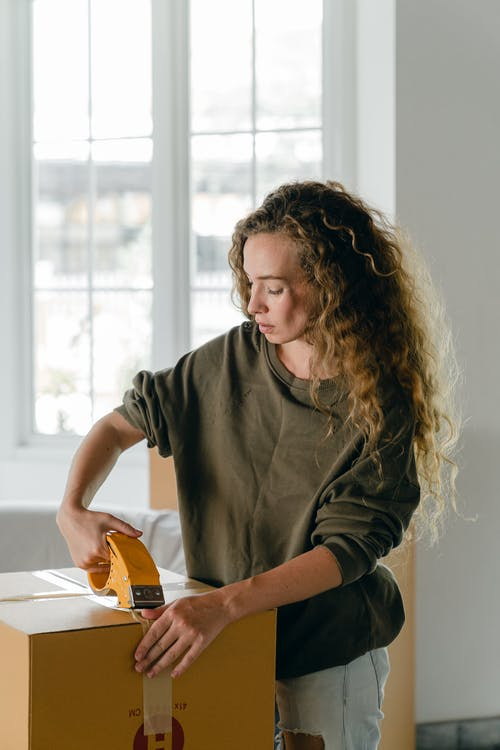 Young concentrated woman taping boxes using packing instrument