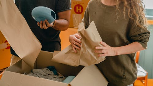 Crop faceless young woman and man unpacking belongings after moving in new house