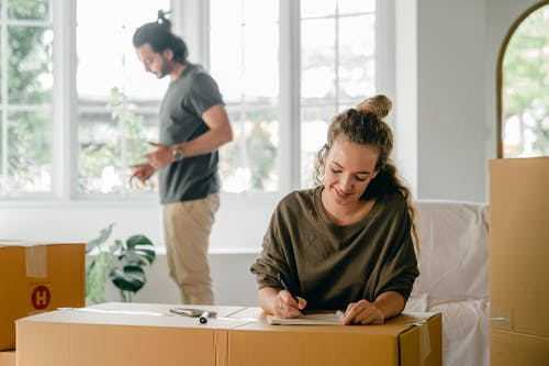Positive young woman writing in notepad while sitting against cardboard boxes during relocation in new house with husband