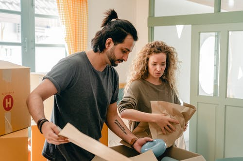 Focused young couple packing boxes together before moving in new house