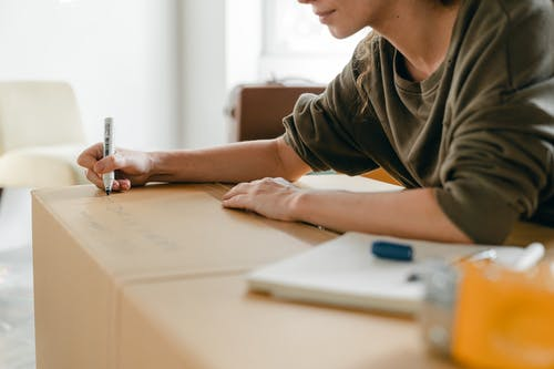 Side view of crop anonymous female in casual wear writing with marker on big cardboard box while sitting near notebook in light flat