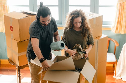 Multiethnic couple packing belongings in parchment near pile of boxes