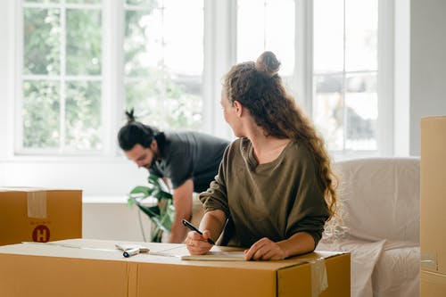 Multiracial couple with pile of boxes preparing to relocate