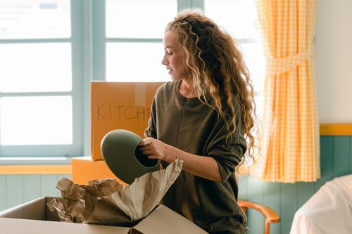 Woman unpacking vase from parchment standing near pile of boxes